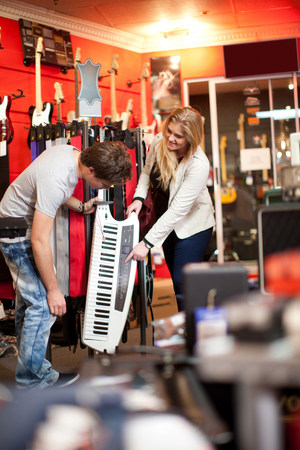 Young couple looking at keytar in music store LANG_EVOIMAGES