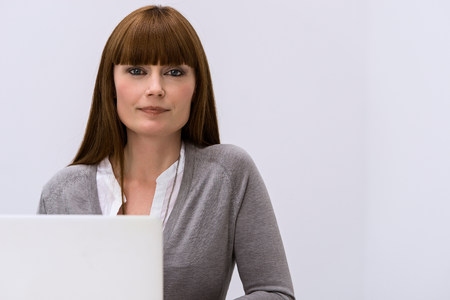 通信: Portrait of mid adult woman at behind laptop