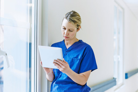 35 to 40 year olds: Doctor standing in corridor looking at digital tablet LANG_EVOIMAGES