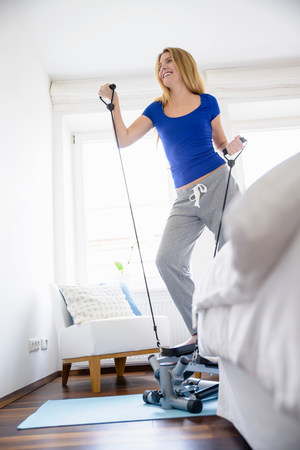 athleticism: Young woman exercising on step machine at home
