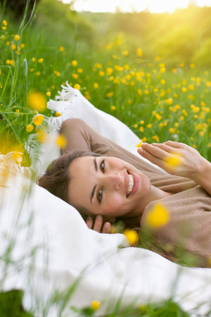 Close up of young woman on picnic blanket with buttercup LANG_EVOIMAGES