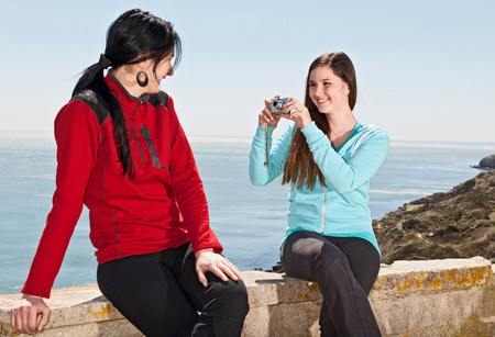 travel features: Teenager photographing friend at the coast