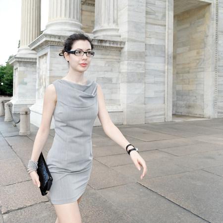 grays: Smart young woman walking along pavement