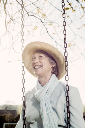 living idyll: Happy senior woman with straw hat on swing looking up