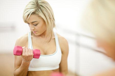 levantar peso: Mujer joven en el entrenamiento de gimnasio con pesas LANG_EVOIMAGES