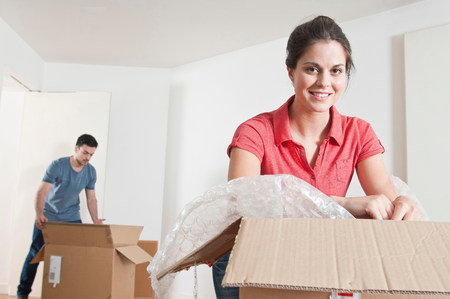 Young couple unpacking cardboard boxes LANG_EVOIMAGES