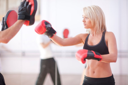 impulsive: Young woman and trainer boxing in gym LANG_EVOIMAGES