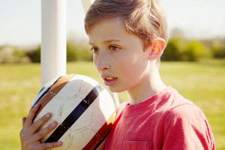shadowed: Boy with ball looking into the distance