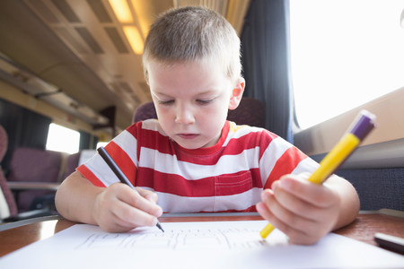 Young boy with pencil,pen and paper on train LANG_EVOIMAGES
