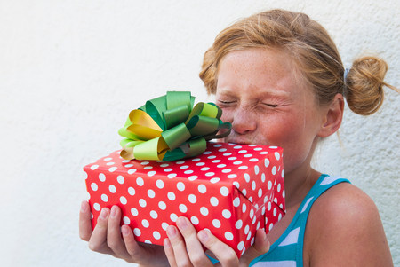 hair wrapped up: Girl kissing gift in hand