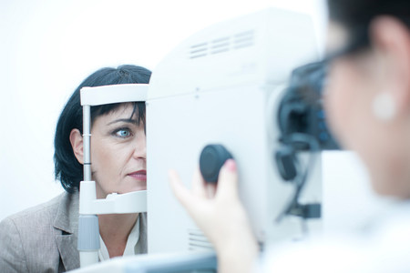 engrossed: Close up of optician monitoring patient in eye clinic LANG_EVOIMAGES