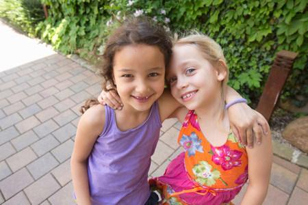 purples: Portrait of two girls hugging LANG_EVOIMAGES