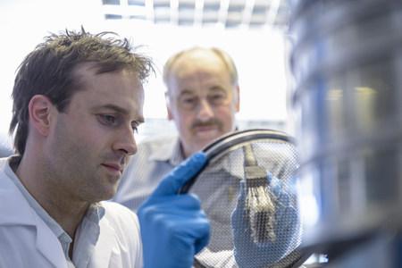Scientist carefully brushing metal sieve LANG_EVOIMAGES