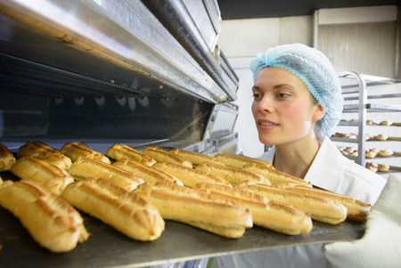 Baker removing tray of baked pastries from oven in bakery LANG_EVOIMAGES