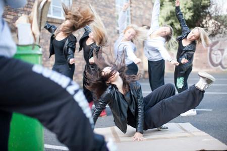 assured: Group of girls breakdancing in carpark