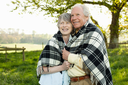 Senior couple wrapped in shawl together LANG_EVOIMAGES