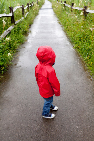 Back view of toddler standing on pathway in red raincoat