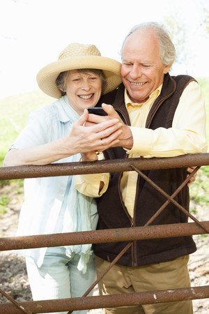 60 65 years: Senior couple smiling at message on mobile phone