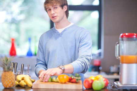 sweatshirts: Young man in kitchen preparing fruit drink
