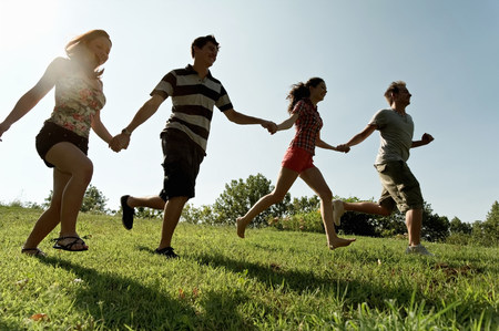Group of young adults holding hands and running LANG_EVOIMAGES