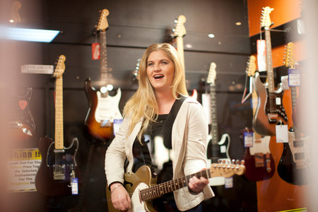 freetime: Young female testing guitar in music store