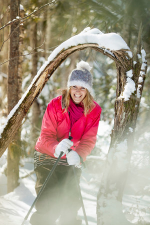 Young adult woman among snow-covered tree branches