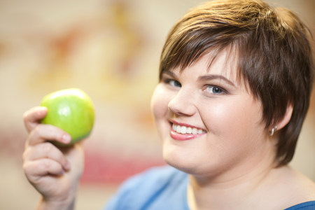 close up food: Close up portrait of young woman holding apple