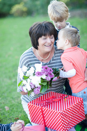 give out: Grandmother with two grandsons and birthday gift