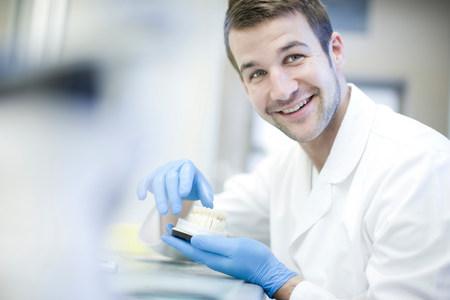 Dental technician holding denture LANG_EVOIMAGES