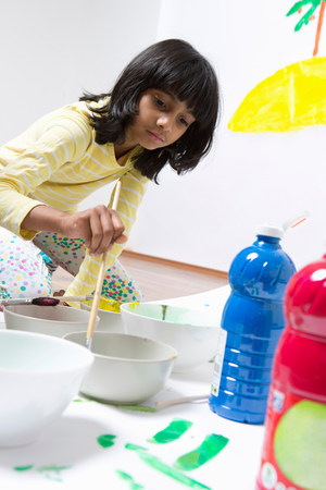 well behaved: Girl kneeling on floor painting LANG_EVOIMAGES