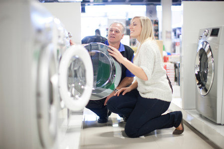 Young woman and salesman looking at washing machines in showroom