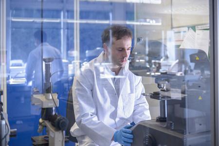 gloved: Scientist working on specialist equipment in laboratory