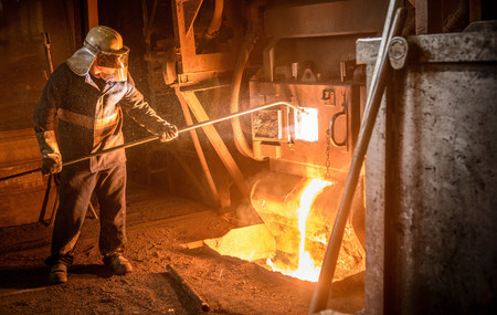 Steel worker and molten metal in steel foundry LANG_EVOIMAGES
