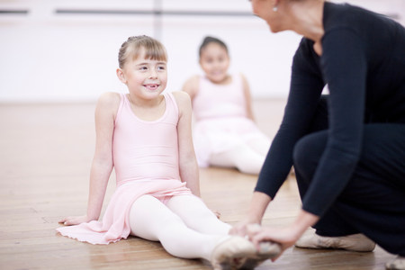 top 7: Teacher adjusting feet position of young ballerina