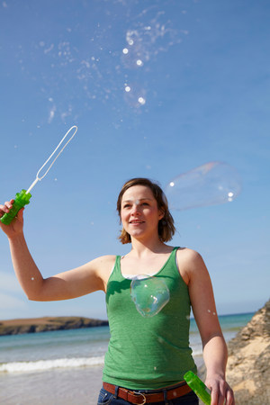 woman hanging toy: Young woman at coast playing with bubble wand