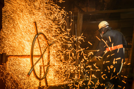 Steel worker amongst sparks in steel foundry LANG_EVOIMAGES