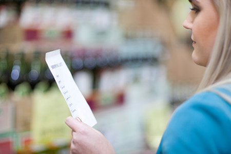 clothing store: Young woman looking at shopping list in supermarket LANG_EVOIMAGES