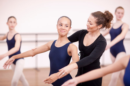 Teacher adjusting arms of shy teenage ballerina