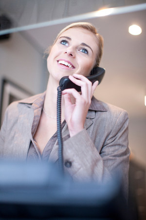 receptions: Receptionist talking on telephone LANG_EVOIMAGES