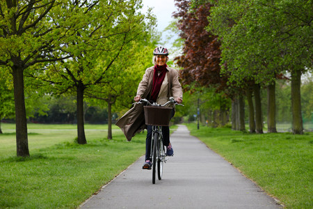 Senior woman riding bicycle in park LANG_EVOIMAGES