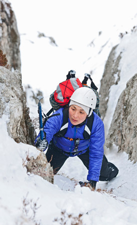 purples: Female climber coming through snow covered ravine,Castell y Geifr,Snowdonia