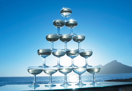 Champagne glasses in pyramid shape with sea in background