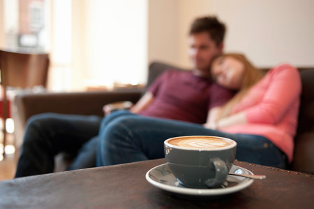 english ethnicity: Young couple lounging on cafe sofa