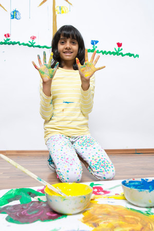 indian subcontinent ethnicity: Girl kneeling on floor finger painting