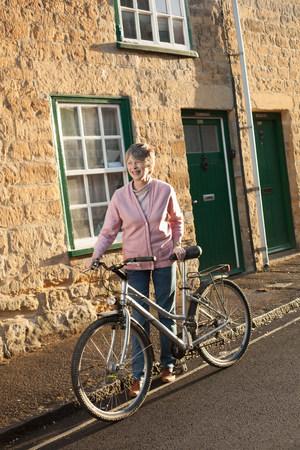 living idyll: Senior man pushing his bicycle on street LANG_EVOIMAGES