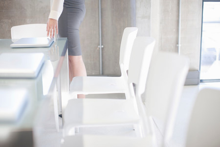 organised: Young woman preparing boardroom table LANG_EVOIMAGES