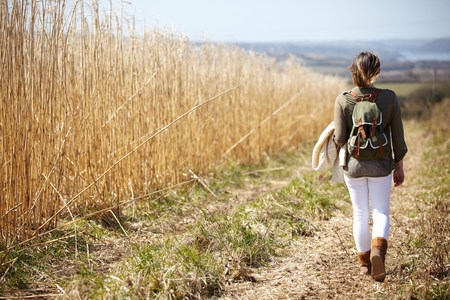 Young woman walking down dirt track next to field of reeds LANG_EVOIMAGES