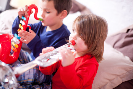 woman hanging toy: Two young children playing toy instruments