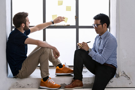 two persons only: Two young male designers sharing ideas on post it notes