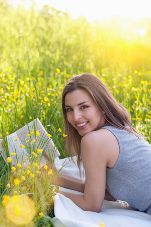 Portrait of young woman reading in field of buttercups